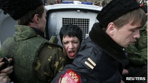 Members of Crimean self-defence units block a topless activist from the Ukrainian feminist group Femen, who is taking part in an anti-war protest near the Crimean parliament building in Simferopol, March 6, 2014.