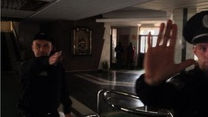 Armed militia signal people to leave inside Crimean parliament in Simferopol on 6 March