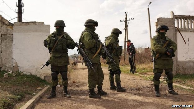 Russian paramilitaries stand guard outside of a Ukrainian military base in the town of Perevevalne near the Crimean city of Simferopol, 6 March