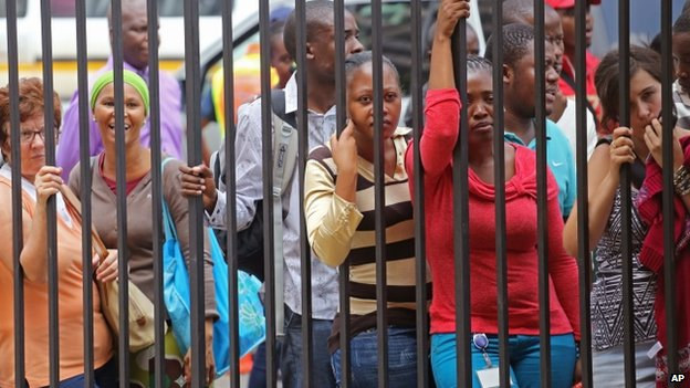 People try to get a view of Oscar Pistorius, during a lunch break from outside the high court, on the fourth day of his trial in Pretoria, South Africa, Thursday, 6 March 2014