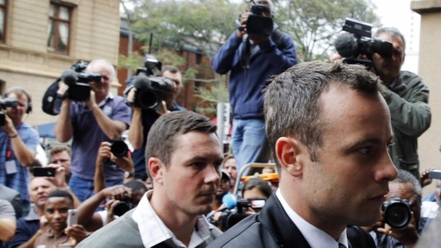 Olympic and Paralympic track star Oscar Pistorius (R) arrives at court ahead of the fourth day of his trial for the murder of his girlfriend Reeva Steenkamp - 6 March 2014
