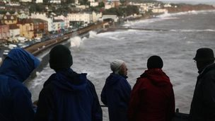 People watch on as waves batter the coast