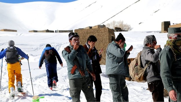 Armed policemen apply sun cream as they gather to provide security for the race in Bamyan