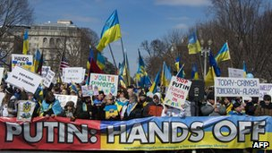 Demonstrators hold placards during a rally against Russian aggression in the Ukraine in front of the White House in Washington DC, on 6 March 2014.