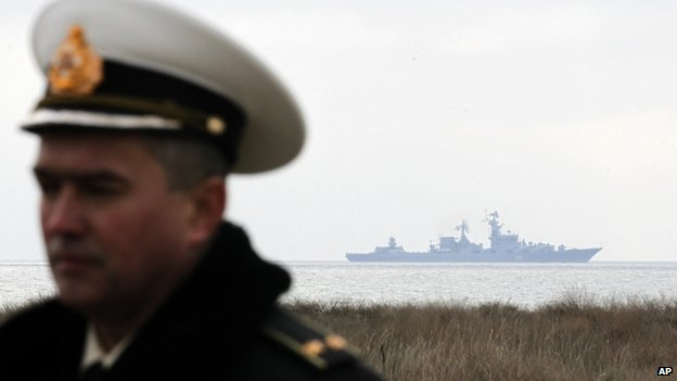 A Ukrainian naval officer stands with the Russian warship Moskva seen behind him in the Black Sea shore off western Crimea, Ukraine - 6 March 2014