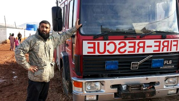 Abdul Waheed Majeed with a truck at a refugee camp