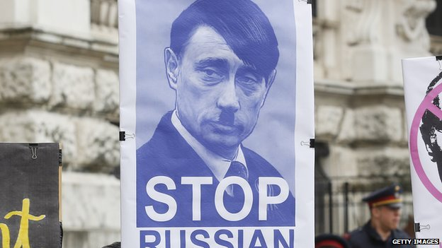 A protestor holds up a sign equating Russian President Vladimir Putin with Adolf Hitler in Vienna on 3 March.