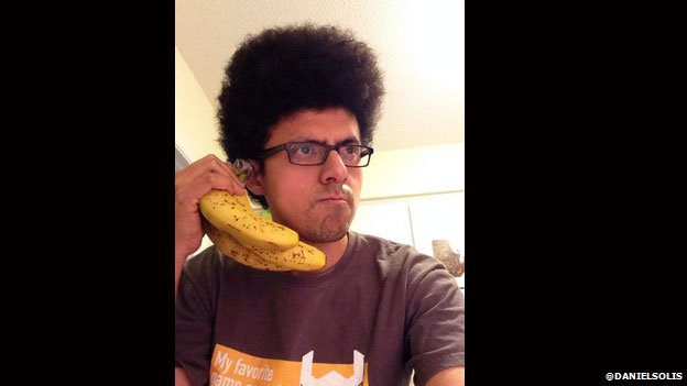 Daniel Solis poses with a bunch of bananas