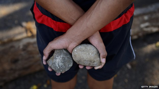 An anti-government activist holds rocks in a barricade set up by anti-government activists in San Cristobal, Tachira state, on 6 March 2014.