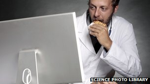 Doctor eating at work whilst using a computer