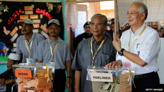 Malaysia's Prime Minister and Barisan Nasional (BN) chairman Najib Razak casts his vote at a polling station during election day on 5 May 2013 in Pekan, Malaysia