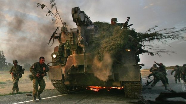 Georgian soldiers flee their burning armoured vehicle during the conflict with Russia in 2008