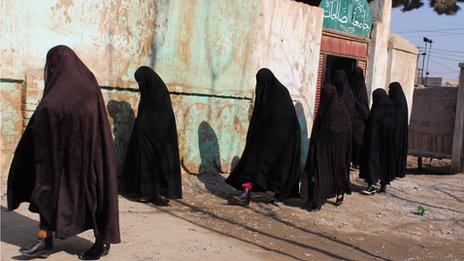 Women walking in front of the Ashraf-ul-Madares madrassa in Kunduz province