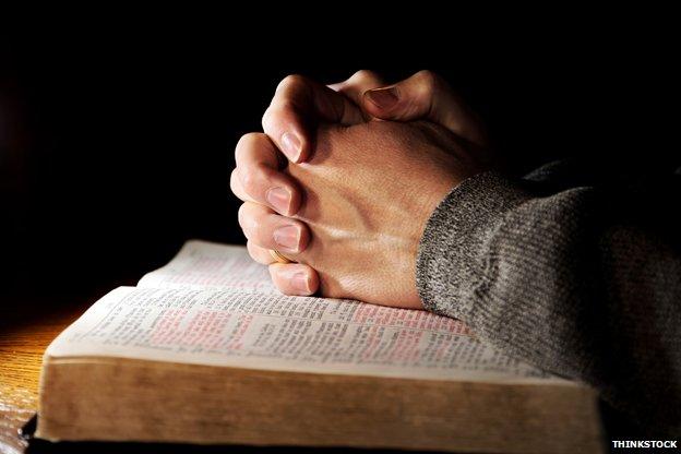 Hands in prayer over Bible
