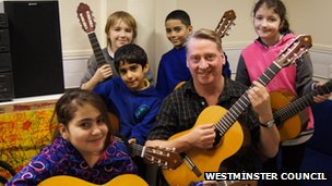 Young people and teacher holding guitars