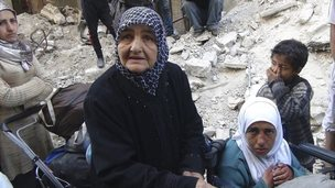 A elderly woman and three young children wait to receive aid in Yarmouk