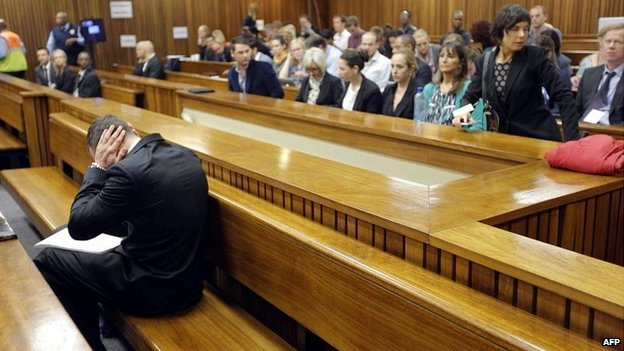 Oscar Pistorius sits in the dock with his head in his hands on day two of his trial