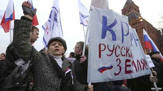 "Protesters carry a banner reading ""Crimea is Russian land!"" at a rally in Moscow (7 March 2014)"