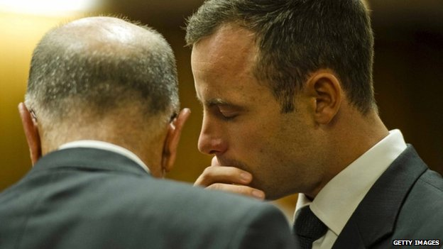 Oscar Pistorius speaks quietly with his uncle Arnold on day five of his trial