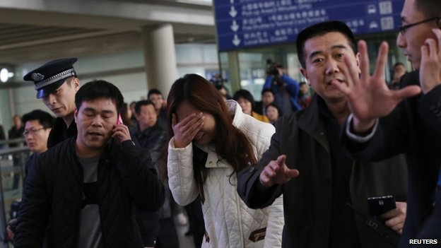 A woman, believed to be the relative of a passenger onboard Malaysia Airlines flight MH370, covers her face as she cries at the Beijing Capital International Airport in Beijing on 8 March 2014