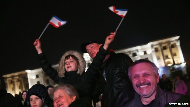 People, including a woman waving Crimean flags, attend an outdoor performance of Russian Crimean folk music on 7 March 2014 in Simferopol, Ukraine