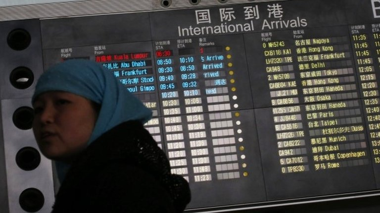 Woman in front of arrivals board at Beijing airport, China (8 March 2014)