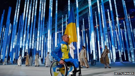 Flag bearer Mykailo Tkachenko of the Ukraine enters the arena during the Opening Ceremony of the Sochi 2014 Paralympic Winter Games on & match 2014