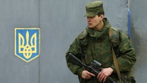 A soldier believed to be Russian stands outside a Ukrainian military base near Sevastopol, 7 March