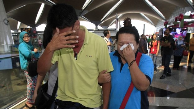 A woman wipes her tears after walking out of the reception centre and holding area for family and friends of passengers aboard a missing Malaysia Airlines plane at Kuala Lumpur International Airport, 8 March