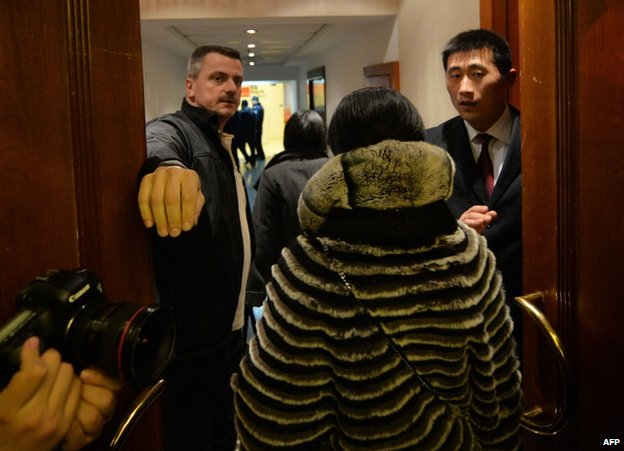 Relatives arrive to meet airline officials at a hotel meeting room following news of the missing Malaysia Airlines Boeing 777-200 plane in Beijing, 8 March