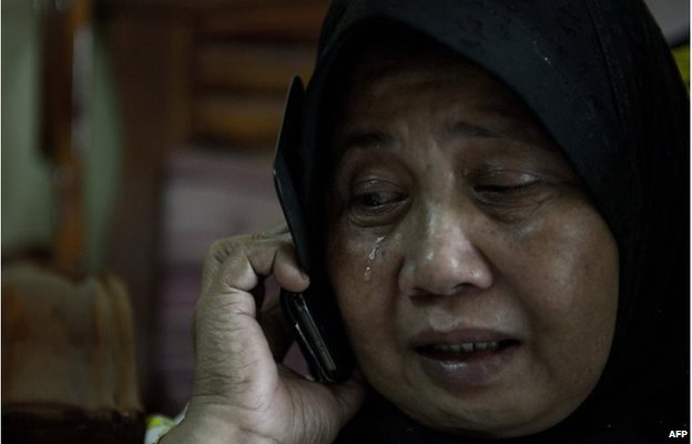A relative of two passengers on the missing plane, cries at their house in Kuala Lumpur