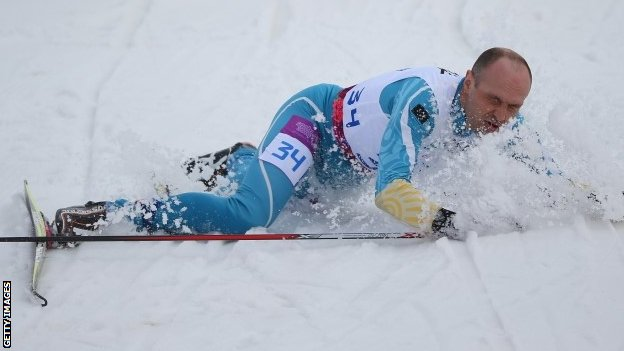 Ukraine's Vitaliy Lukyanenko falls over as he crosses the finish line to win the visually impaired biathlon