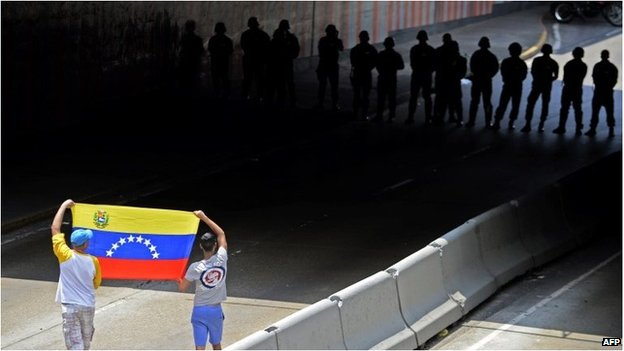 Protesters hold Venezuelan flag before line of security force members