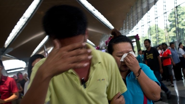 A woman and man break down while leaving the reception centre for families and friends after an airliner went missing at the Kuala Lumpur International Airport on 8 March 2014.