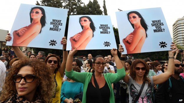 Lebanese women hold posters to mark International Woman's Day during a rally of thousands demanding that parliament approves a law that protects women from domestic violence, in Beirut, Lebanon, on 8 March 2014