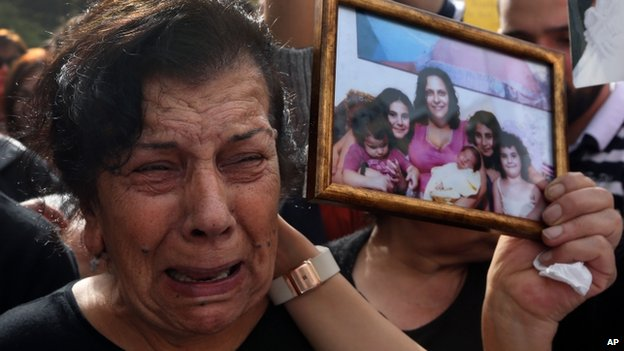 The mother of Roula Yaacoub, who her family says was killed by her husband last year, carries a picture of her daughter and grandchildren while taking part in a rally against domestic violence in Beirut, Lebanon, on 8 March 2014.
