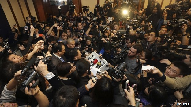 A spokesman (C) of Malaysia Airlines is surrounded by journalists as he gives a briefing about Malaysia Airlines flight MH370, at a hotel in Beijing March 8, 2014