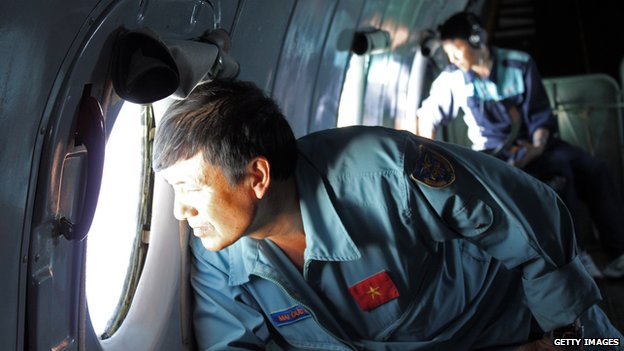 Military personnel scanning the sea aboard a Vietnamese Air Force aircraft taking part in a search mission for a missing Malaysia Airlines aircraft on 8 March 2014