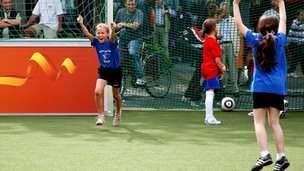 Girls celebrate scoring a goal in football