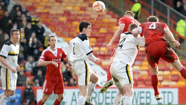 Adam Rooney rises above the Dumbarton defence to head Aberdeen in front.