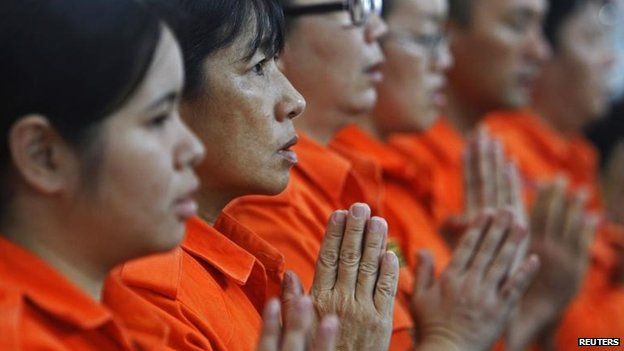 Rescue workers from a Buddhist organisation pray during multi-religion mass prayers for the passengers of Malaysian Airlines flight MH370, 9 March