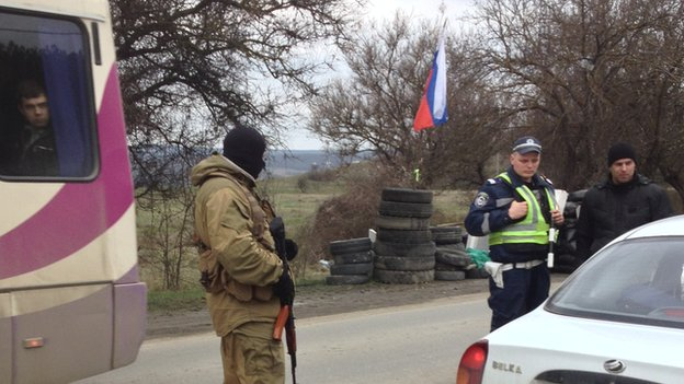 An armed man and a policeman check a car in Crimea