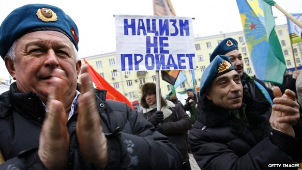 Former Russian paratroopers applaud during a pro-Russian rally in the Ukrainian region of Crimea
