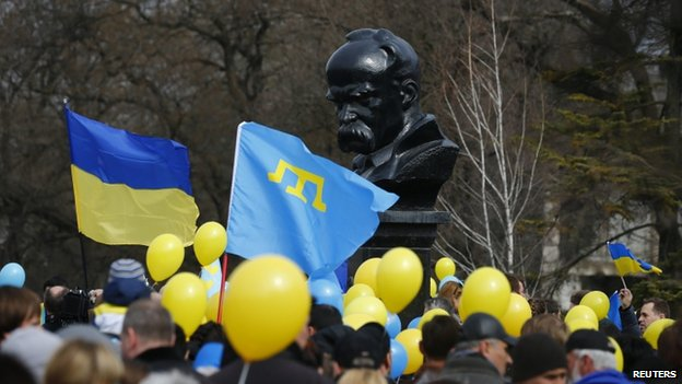 Pro-Ukrainian supporters wave flags near a monument to Ukrainian poet Taras Shevchenko at a rally in Simferopol