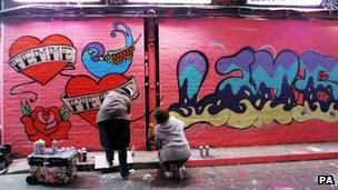 Cleo Jones from Devon (left) and Josephine Hobbs from Twickenham (right) take part in a graffiti artists attempt to create the worlds largest mural at the Leake Street Tunnel in Waterloo, London.
