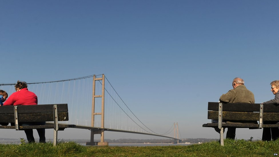 People sitting alongside the Humber estuary, near Kingston upon Hull