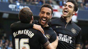 Wigan players celebrate beating Manchester City