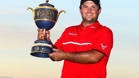 Patrick Reed holds aloft the WGC-Cadillac Championship trophy