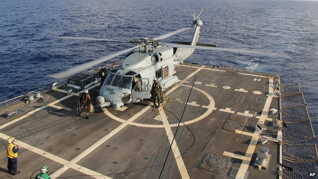 A U.S. Navy helicopter lands aboard Destroyer USS Pinckney during a crew swap before returning to a search and rescue mission for the missing Malaysian airlines flight MH370 in the Gulf of Thailand, Sunday, March 9, 2014
