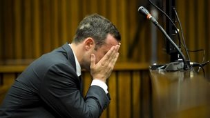 Oscar Pistorius holds his head in court